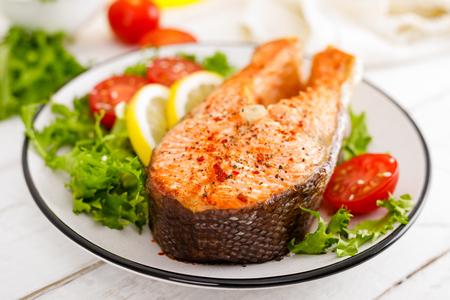 Foto de Salmon fish steak grilled and fresh vegetable salad with tomato and lettuce. Healthy food. Top view - Imagen libre de derechos