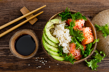 Photo pour Hawaiian poke coconut bowl with grilled salmon fish, rice and avocado. Healthy food. Top view - image libre de droit