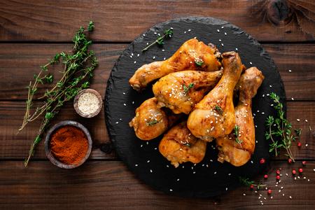 Photo pour Grilled chicken legs on wooden background. Top view - image libre de droit