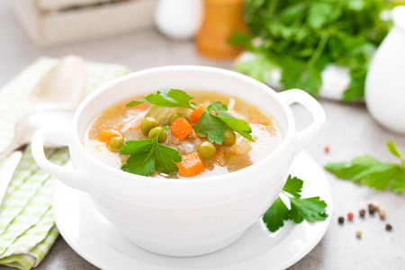 Foto de Summer light vegetarian vegetable soup with carrot, potato, cabbage and grean peas on white background. Diet healthy and tasty lunch. Baby food - Imagen libre de derechos