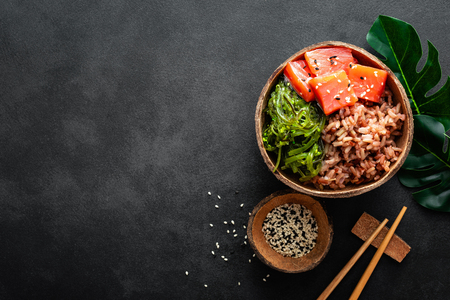 Photo for Poke bowl with raw salmon fish, chuka salad and rice in coconut bowls on black background - Royalty Free Image