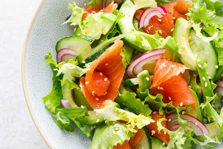 Photo pour Salmon avocado salad with salted fish, lettuce, red onion and cucumbers - image libre de droit