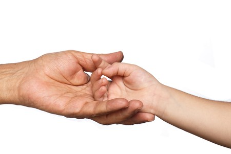 A senior persons hand cradling a young boys hand