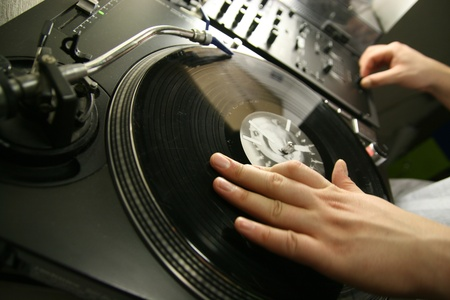 scratch battle of dj playing on his vinyls hand on