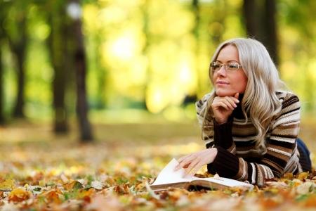 Photo pour woman read the book in autumn park - image libre de droit