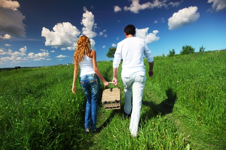 Photo for man and woman walk on picnic in green grass - Royalty Free Image