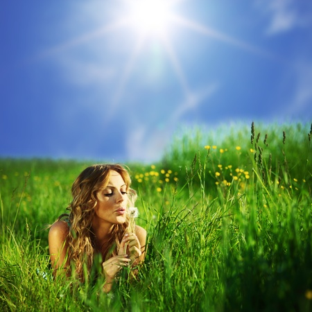 Photo for girl blow on dandelion on green field - Royalty Free Image