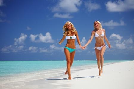 Two girls run along the ocean coast