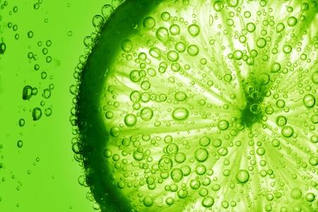 Foto de lime slice in water bubbles - Imagen libre de derechos