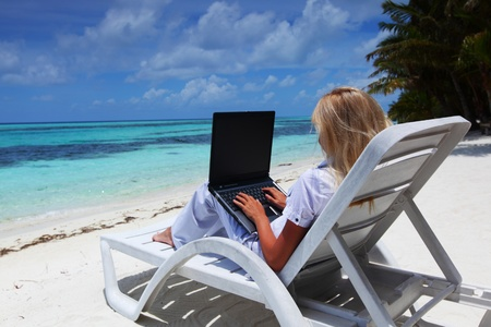 business woman with laptop lying on a chaise lounge in the tropical ocean coastの写真素材