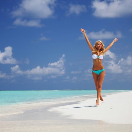 happy girl run along the ocean coast