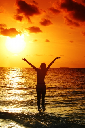 happy woman standing on a sunset in ocean wavesの写真素材