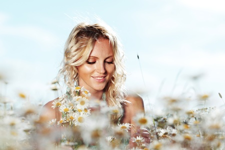beautiful girl on the daisy flowers field の写真素材