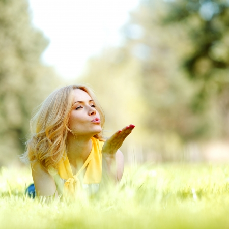 Happy young woman lying on grass and blowing kiss