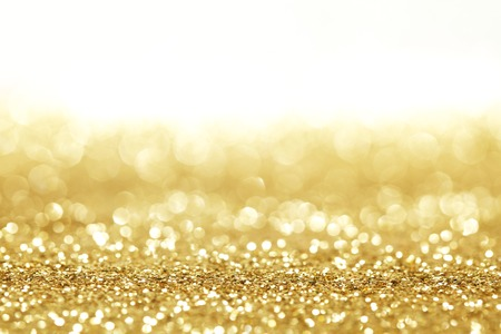 Golden shiny glitter holiday celebration background with white copy spaceの写真素材