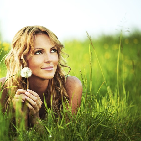 Young woman with dandelion lying on grass