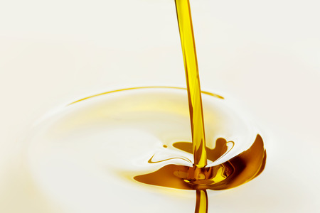 Pouring liquid golden oil close up view