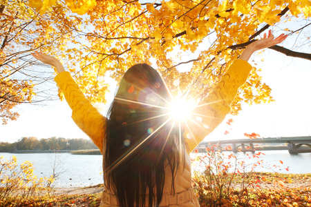 Photo pour Happy woman with raised hands in autumn park - image libre de droit