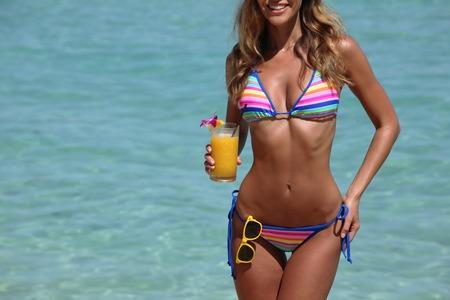 Photo pour Beautiful woman in bikini with cocktail on beach - image libre de droit