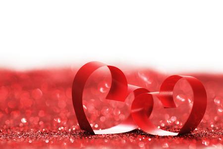 Foto de Red ribbon hearts on glitters isolated on white, Valentines day concept - Imagen libre de derechos