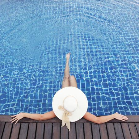 Photo pour Woman in hat relaxing at the pool - image libre de droit