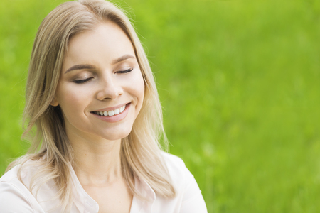 Photo pour A beautiful young woman on grass enjoy nature smiling with closed eyes - image libre de droit