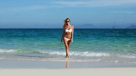 Photo pour Pretty smiling girl in bikini walking at tropical sea beach - image libre de droit