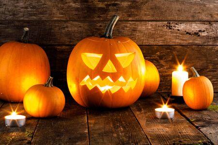 Photo pour Halloween pumpkin head jack o lantern and candles on wooden background - image libre de droit