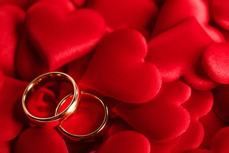 Photo pour Two golden wedding rings on red satin hearts background - image libre de droit