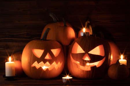 Foto de Halloween pumpkin head lanterns and burning candles on wooden background - Imagen libre de derechos