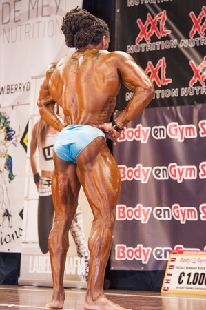 SCHIEDAM, THE NETHERLANDS - APRIL 26, 2015. Male bodybuilder Grego Francisca shows his best lats spread pose at the 38th Dutch National Championship Bodybuilding and Fitness of the IFBB Netherlands (NBBF) on april 26, 2015 in Theatre aan de Schie at Sch