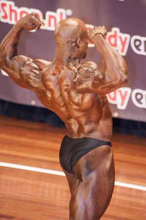 SCHIEDAM, THE NETHERLANDS - APRIL 26, 2015. Male bodybuilder shows his best back double biceps pose on stage at the 38th Dutch National Championship Bodybuilding and Fitness of the IFBB Netherlands (NBBF) on april 26, 2015 in Theatre aan de Schie at Sch