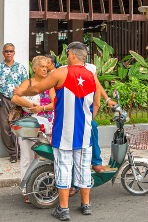 Cuban people conversing on the street, one man wearing clothes with the Cuban flag.