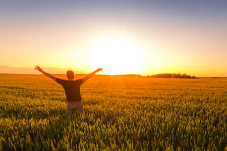Photo for A man with his hands raised up against the backdrop of a sunset or dawn in a rye field. The concept of success, happiness, active lifestyle and outdoor recreation. - Royalty Free Image