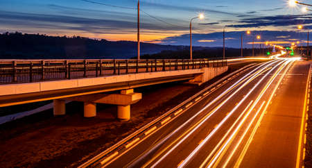 Photo for Traces of headlights from cars moving at night on the bridge, illuminated by lanterns. Abstract cityscape with highway at dusk. - Royalty Free Image