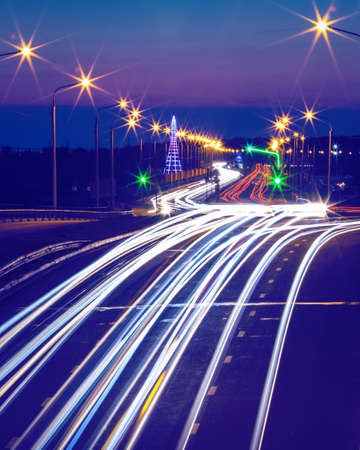 Foto de Traces of headlights from cars moving at night on the bridge, illuminated by lanterns. Abstract city landscape with highway at dusk. - Imagen libre de derechos