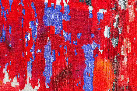 A fragment of colorful graffiti painted on a wooden board with peeling paint close-up. Abstract background for design.