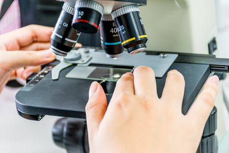 Close up view of scientist hands with a slide ofthe sample in the microscope for research in laboratory