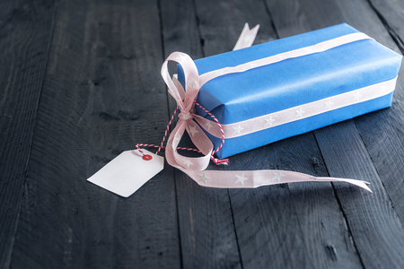 Stylish gift box, wrapped in blue paper and tied with pink ribbon and bow, with an empty etiquette attached to it, on a vintage background.