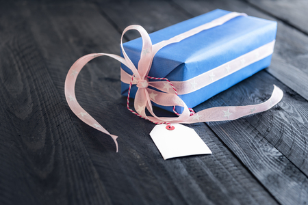 Classy blue gift, tied with pink ribbon and bow, with an empty label tied to it, on an old wooden table.