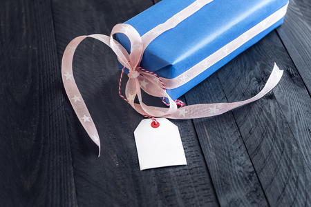 Chic present, wrapped in blue paper and tied with pink ribbon and bow, with an empty label attached to it, on a black wooden table.