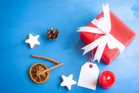 Xmas image with cinnamon sticks, star shaped cookies, dried orange, a lit candle and a lovely red gift tied with white ribbon and bow on a blue wooden table.
