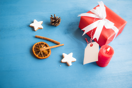 Gift, wrapped in red paper and tied with white ribbon and bow, with a blank tag attached to it, surrounded by cinnamon sticks, dried orange and star shaped cookies.