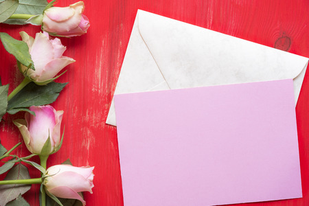Greeting card idea with a pink paper on a closed envelope, surrounded by roses on a red wooden background. A concept for mother day, valentine day and events.