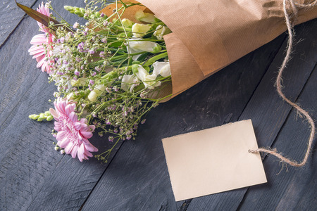 Greeting card idea with a cheerful bouquet of flowers wrapped in vintage brown paper and an empty etiquette tied to it, on a rustic wooden table.
