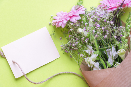 Gifting theme photo with a bouquet of mixed flowers and a message card tied to it, on a green background. A concept for celebrations, events, valentine and mother day.
