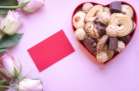 Love theme image with a heart shaped box full of delicious cookies and chocolate, lovely pink roses and an empty piece of paper for a thoughtful message.