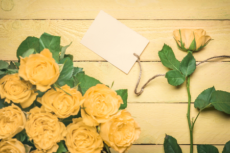 Greeting card idea with roses bouquet and a separate rose with a blank message card attached to it with a linen string, on a yellow wooden table.