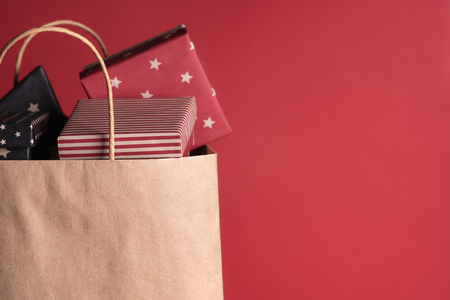 Foto de Shopping paper bag full of gifts wrapped in black and red paper, on a red background. - Imagen libre de derechos