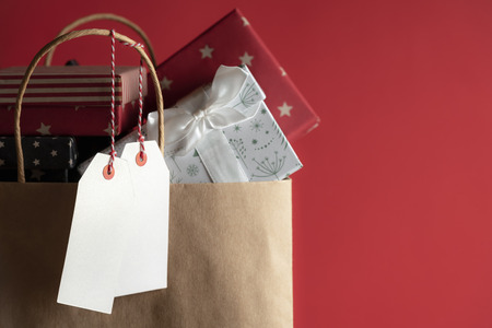 Two white unwritten labels hanging from a paper bag full of colorful gift boxes, on a red background.
